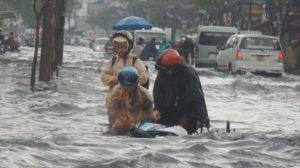 Phần lớn phụ huynh phải tự lo liệu việc đưa đón con đi học. Trong ảnh: Một phụ nữ đón hai con đi học về bị té ngã do mưa ngập trên đường Hòa Bình, Q.11, TP.HCM - Ảnh: Đ.Phú